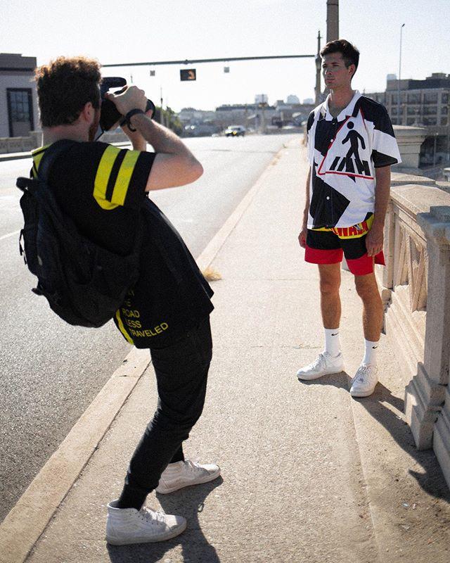 Man Taking Picture of Man Wearing Walk The Walk Brand